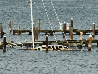 storm damaged dock and sunken sailboat